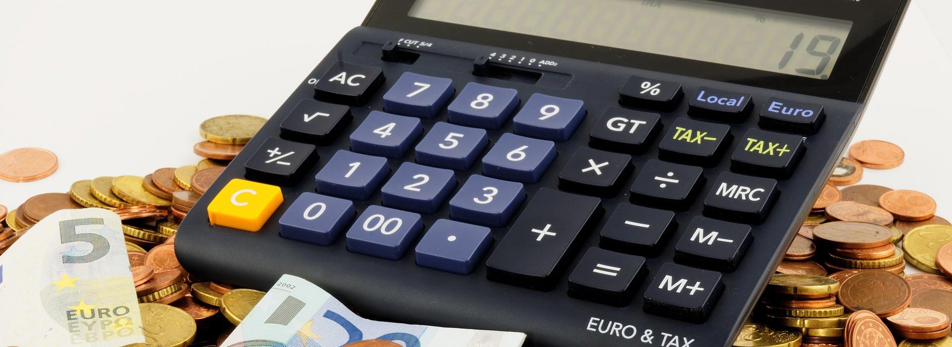 Ausschnitt eines Taschenrechners der auf einem Haufen Geldmünzen liegt