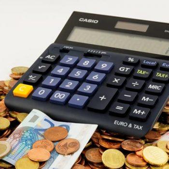 Taschenrechner auf Geldmünzenhaufen